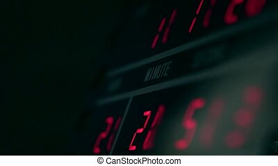 Digital clock in dark room with red glowing digits -...