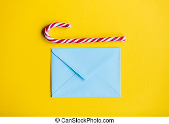 Blue christmas envelope and lolipop on yellow background