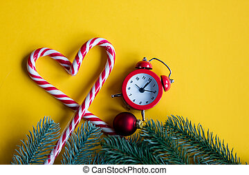 christmas alarm clock  and lolipop on yellow background