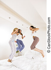 Young women jumping on the bed - Three pretty young happy...