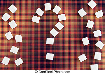 Sugar cubes shaped as a question mark on red squared...
