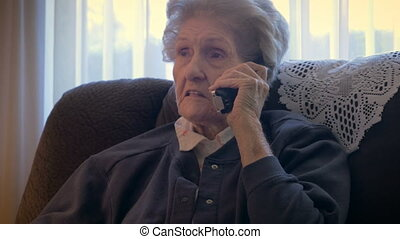 An aging senior in her 90s talks and laughs on a phone in...