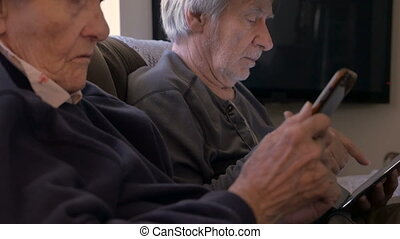 90 year old women and son look on their mobile devices, a cell phone and tablet