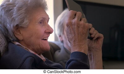 """""""An older woman in her 90s looks at a digital tablet, laughing and smiling"""""""