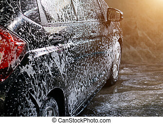 Selective focus of Black Car wash with soap and sunlight...
