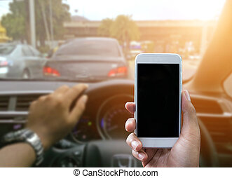 Using a smartphone while driving a car - Man using a...