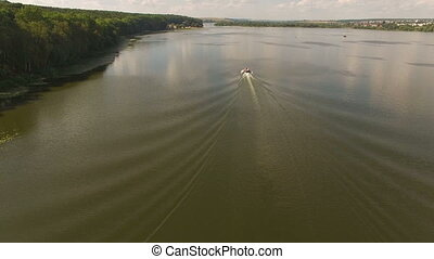 Aerial view of the cutter moving on the river, bach and...