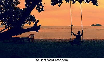 Silhouette of beautiful girl relaxing on a swing at the beach