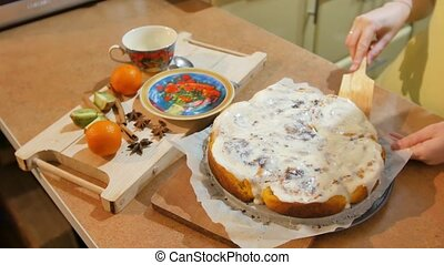 Woman lays on a plate piece of fresh baked Cinnabon and...