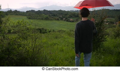 A man with a red umbrella walks off into the distance in a rural setting