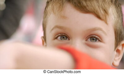 Close up of a cute young boy's eyes peeking from behind his...