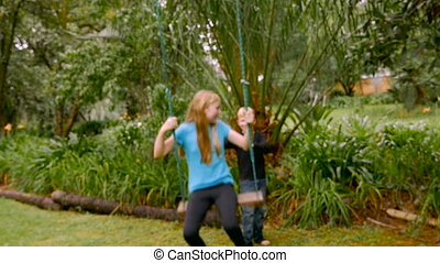A young tween blond girl opens her arms while swinging on a...