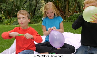 Three young kids blow up and tie off balloons outside - slowmo handheld