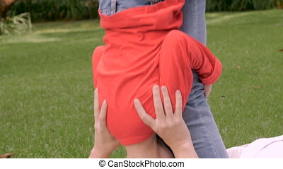 A mother plays with her young son outside in a park- slow...