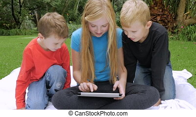 Three young children play together on a single tablet outside - slowmo handheld