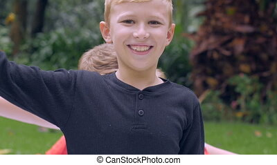 A cute smiling young blond boy waives his arms with others waving behind him