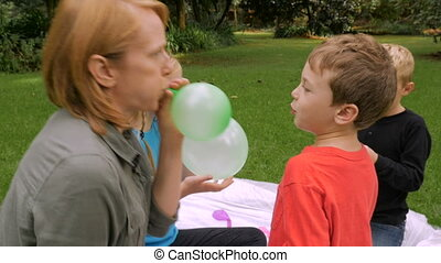 A mother blows up a balloon for her son at a picnic - slowmo handheld