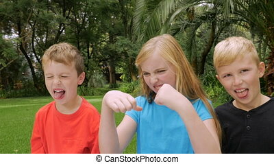 A family of three children expressing yuck and giving thumbs...