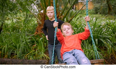A young boy sits on tree swing by himself with a boy behind him - slowmo