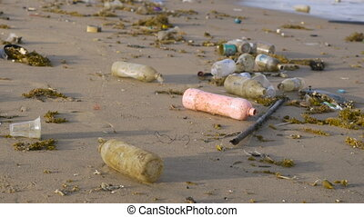 Plastic bottles littering the coast line of a beach and in...
