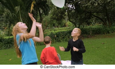 A family starts a simple game of hitting balloons in the air - slowmo