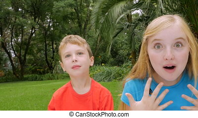 Three children are surprised outside in a park