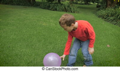 A young boy in a red shirt with red hair plays outside with...