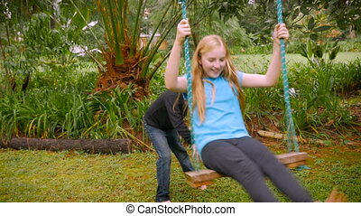 A little boy pushes a young girl on a swing in a park - slowmo