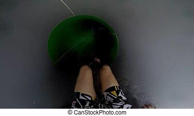 Enjoyment on the water slide in aqua park. Legs in green water slide.
