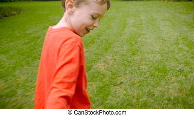 A happy young boy pulling someone while running through the grass - slowmo
