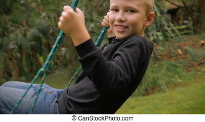 A adorable blond haired boy swinging on a swing looking at the camera - slowmo