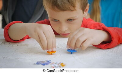 "A boy uses both hands to spin two spinning tops - ""A boy..."
