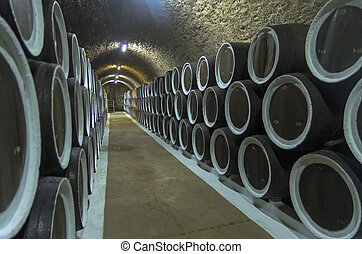 Oak barrels with wine in the winery cellars. Crimea. - Oak...