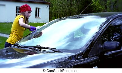 Portrait Of Woman Washing Car in house yard.