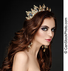 Beautiful brunette girl with a golden crown, earrings and...