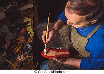 businessman working hard at his atelier - bootmaker holding...