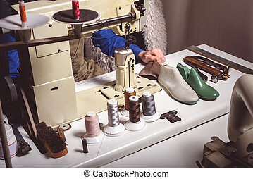 tailor working in the atelier - sewing machine with thread...