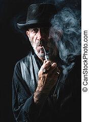 Smoking the pipe - Portrait of senior man smoking the...