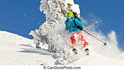 Freeride skier in powder snow running downhill - Freeride...