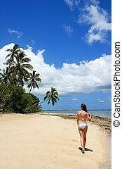 Young woman in bikini walking on the beach at Makaha'a...