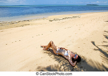 Young woman in bikini lying on the beach on Makaha'a island...