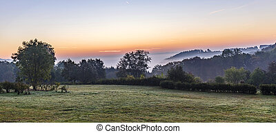 sunrise in german countryside with hills in the Eifel -...