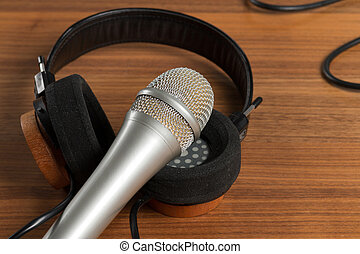 Elegant headphones and a studio microphone on a wooden table