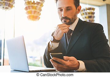 Serious man using smartphone in cafe - Smart businessman is...