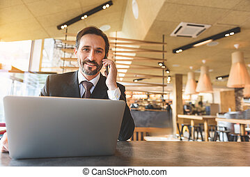 Successful businessman using smartphone for communication -...