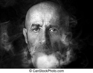 Man blowing smoke, portrait in low key and black and white
