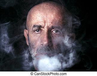Man blowing smoke, portrait in low key
