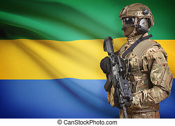 Soldier in helmet holding machine gun with flag on...