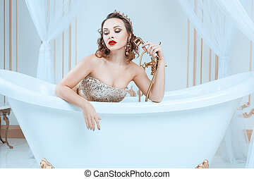 Queen sitting in the bath. - Queen sitting in a bathtub with...