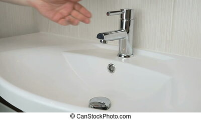 Person washing hands in the bathroom. Close up